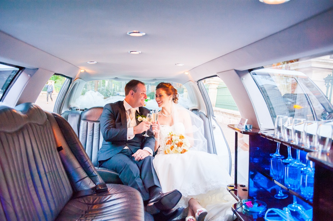 bride and groom in 12 seat wedding car